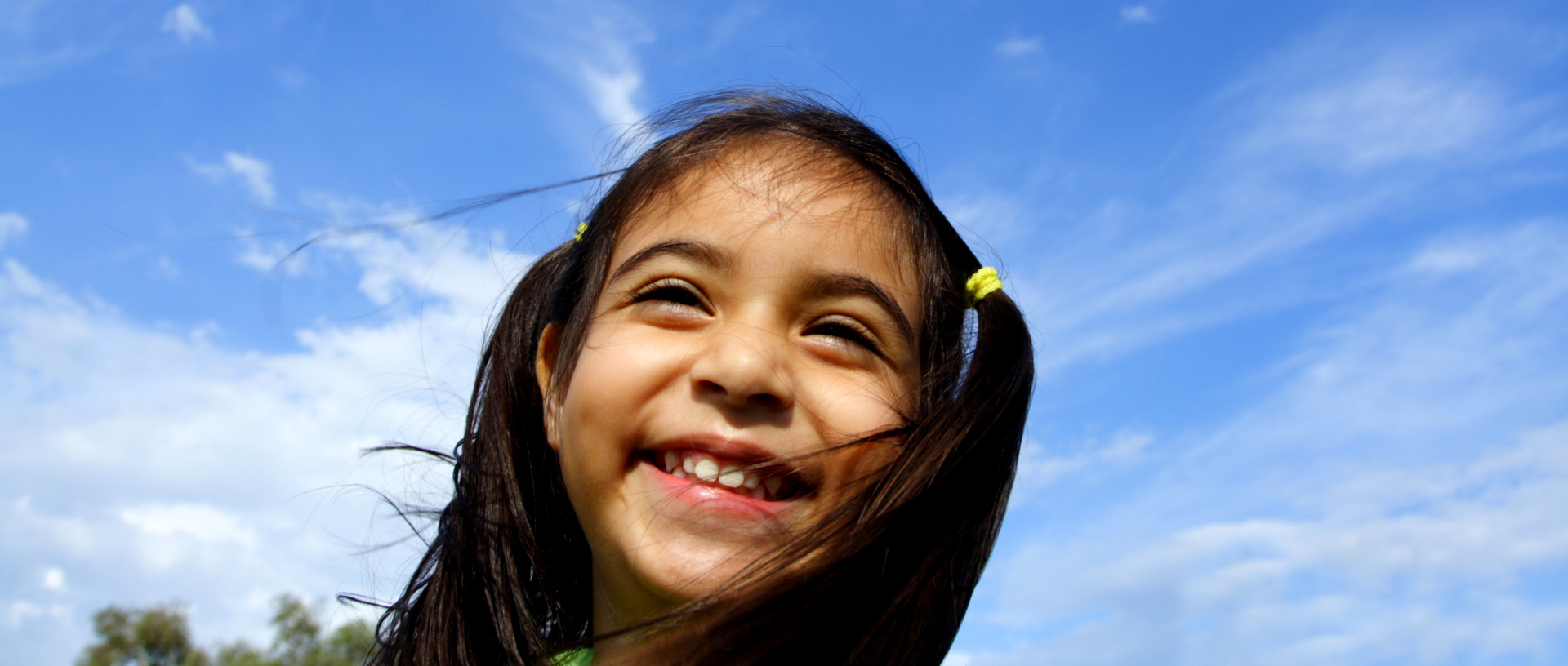 Girl Smiling while outside at the park with blue sky background