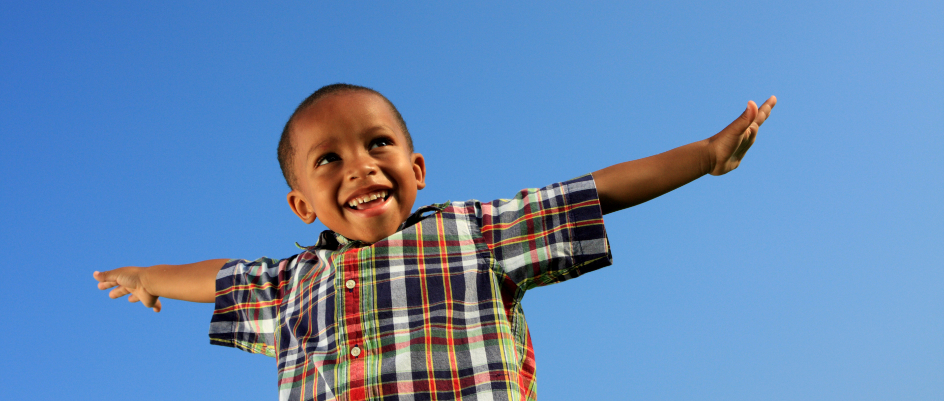 Young child pretending to fly with blue sky background.
