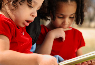 Beautiful multiracial children with afro hairstyle reading a book