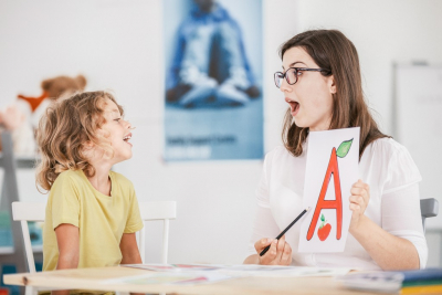 therapist working with a child on a correct pronunciation